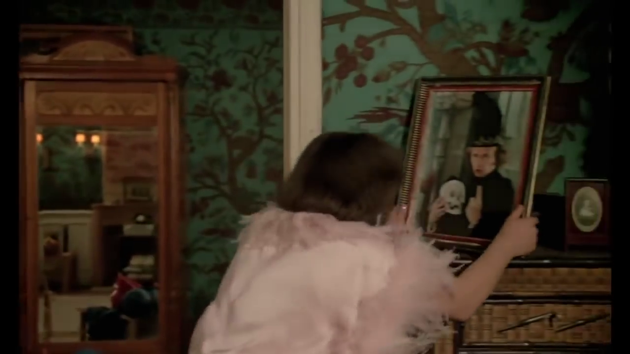 Josyane breaks the framed picture of Grégoire as Hamlet.
